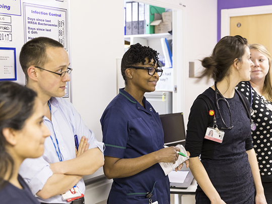 Doctors And Nurses Gathered In Hospital Corridor Meeting At Uclh