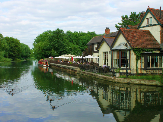 Pub By River In English Countryside
