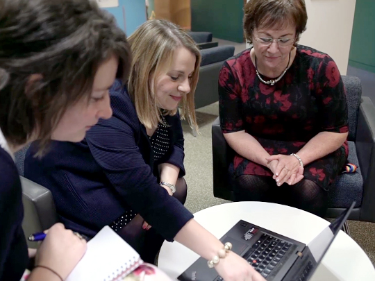 Three Women In Finance Sitting Around Laptop On Table
