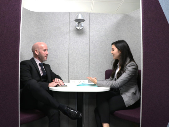 Two Counter Fraud Team Members In A Booth