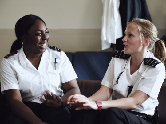 Two Prison Officers Talking On Sofa