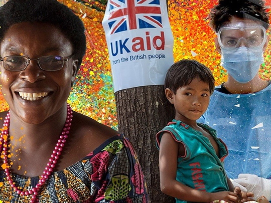 Uk Aid Woman Smiling Boy Leaning Against Tree Woman In Protectice Laboratory Wear