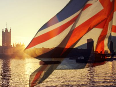 Union flag blowing in the wind at sunset across from the houses of parliament
